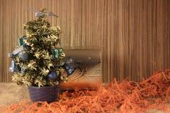En liten julgran på en träbakgrund för vykort och Arkivbild