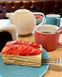 En liten kaka med jordgubbar, på tabellen, nära kokkärlet och rånar royaltyfria bilder