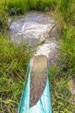 En liten kanal bredvid en liten väg kommer med vatten till risfältet Royaltyfri Fotografi