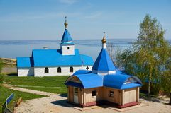 En liten kyrka som målas med blått, målar mot bakgrunden av havet och den blåa himlen på en solig dag royaltyfri fotografi