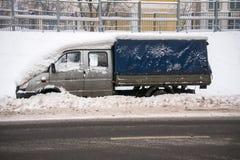 En liten lasttältskåpbil som täckas med det tjocka lagret av snö och gyttja, på körbanan royaltyfri fotografi