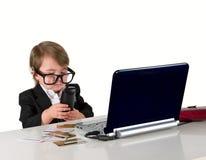 En liten liten flicka (pojke) med exponeringsglas, dator och krediterar ca Arkivfoton