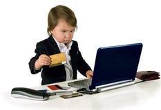 En liten liten flicka (pojke) med ringer, datoren och kreditkorten Arkivfoto