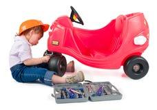 En liten liten flicka som reparerar toybilen. Arkivfoto