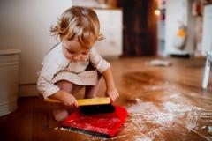 En liten litet barnflicka med borsten och sopskyffel som hemma sopar golvet i köket arkivbilder