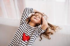 En liten lycklig flicka i den randiga T-tröja hemma som har gyckel Arkivbild