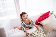 En liten lycklig flicka i den randiga T-tröja hemma som har gyckel Arkivfoton