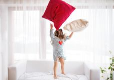 En liten lycklig flicka i den randiga T-tröja hemma som har gyckel Royaltyfria Foton