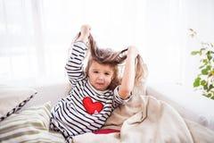 En liten lycklig flicka i den randiga T-tröja hemma som har gyckel arkivbilder