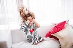 En liten lycklig flicka i den randiga T-tröja hemma som har gyckel Arkivfoto