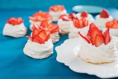 En liten marängPavlova efterrätt med några jordgubbeskivor Royaltyfri Fotografi
