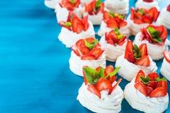 En liten marängPavlova efterrätt med några jordgubbeskivor med mintkaramellsidor på en blå bakgrund royaltyfri foto