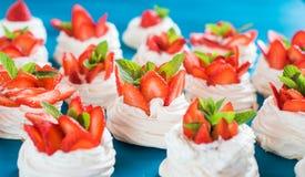 En liten marängPavlova efterrätt med några jordgubbeskivor med mintkaramellsidor på en blå bakgrund Arkivfoton