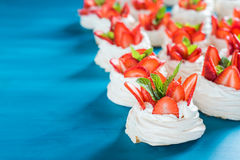 En liten marängPavlova efterrätt med några jordgubbeskivor med mintkaramellsidor på en blå bakgrund Royaltyfri Fotografi