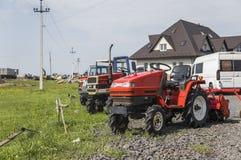 En liten mini- röd traktor står på en lantgårdgård på grönt gräs och väntar på arbete för att börja mot en andra traktorer och arkivfoto