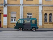 En liten minibuss står på gatan arkivbilder
