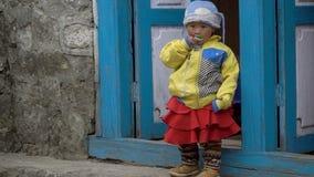 En liten nepalesisk flicka äter godisen stock video