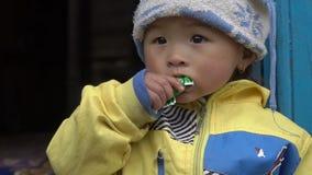 En liten nepalesisk flicka äter godisen lager videofilmer