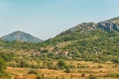 En liten by och byggnader i de gröna Balkan bergen av Montenegro Arkivbilder