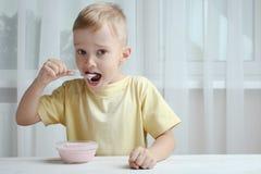 En liten pojke äter yoghurt arkivfoto