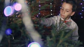 En liten pojke dekorerar en julgran lager videofilmer