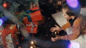 En liten pojke dekorerar en julgran arkivfilmer