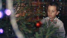 En liten pojke dekorerar en julgran stock video