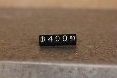 En liten prislapp förläggas på golvet arkivfoto