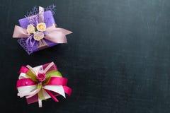 En liten purpurfärgad gåvaask med rosor och ribon och den andra pi arkivbilder