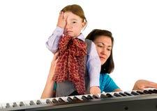 En liten pys som spelar pianot. Arkivbild