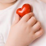 En liten röd hjärta i hand av barnet Förälskelse Lycka omsorg Sjukvård Barndom arkivbild