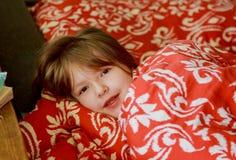 En liten sjuk flicka i sovrummet Liten flickasammanträde på bära för säng pyjamas Royaltyfri Bild