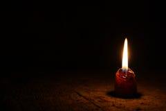 En liten stearinljus i ett mycket mörkt rum på de gamla brädena Royaltyfri Foto