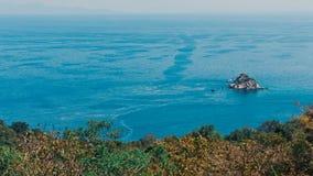 En liten stenig ö i havet Arkivfoto