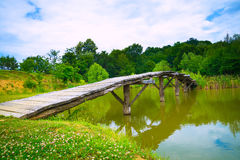 En liten träbro över en flod fotografering för bildbyråer