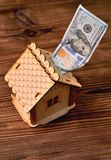 En liten trähus-piggy bank och en pengarräkning av 100 dollar Royaltyfri Foto