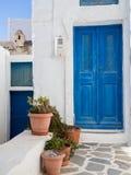 En liten traditionell blå dörr med några lerakrukor framme royaltyfri foto