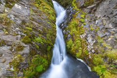 En liten vattenfall i bergen mellan två mossa-täckte klippor royaltyfria foton