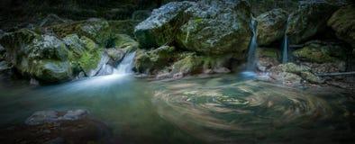 En liten vattenfall i skogen Arkivbilder