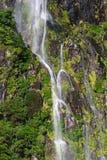 En liten vattenfall på Milford Sound Royaltyfri Fotografi