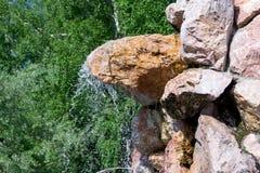 En liten vattenfall strilar droppar av vatten - ner royaltyfri foto