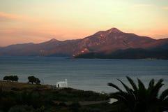 En liten vitkyrka på den Aegean kusten på solnedgången Arkivbild