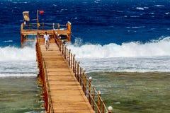 En livräddare Walking Along Pier Among de lösa vågorna på Calimera Habiba Beach Resort arkivbild