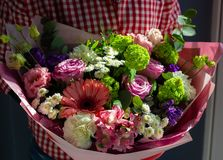 En ljus bukett av nya blommor i händerna av en ung flicka arkivfoto