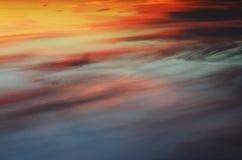 En ljus och färgrik solnedgång i himlen som täckas med moln Arkivfoton