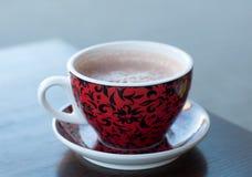 En ljus röd och svart kopp av kakao på en trätabellyttersida Fotografering för Bildbyråer