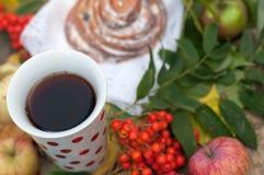 En ljus sammansättning för A med en kopp av starkt svart te, en söt bulle med russin, askabär, äpplen och färgrika höstsidor på Royaltyfria Bilder