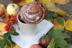 En ljus sammansättning för A med en kopp av starkt svart te, en söt bulle med russin, askabär, äpplen och färgrika höstsidor på Fotografering för Bildbyråer