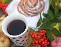 En ljus sammansättning för A med en kopp av starkt svart te, en söt bulle med russin, askabär, äpplen och färgrika höstsidor på Arkivbild