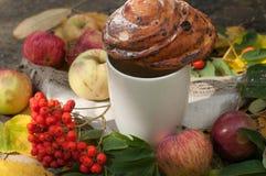 En ljus sammansättning för A med en kopp av starkt svart te, en söt bulle med russin, askabär, äpplen och färgrika höstsidor på Royaltyfria Foton